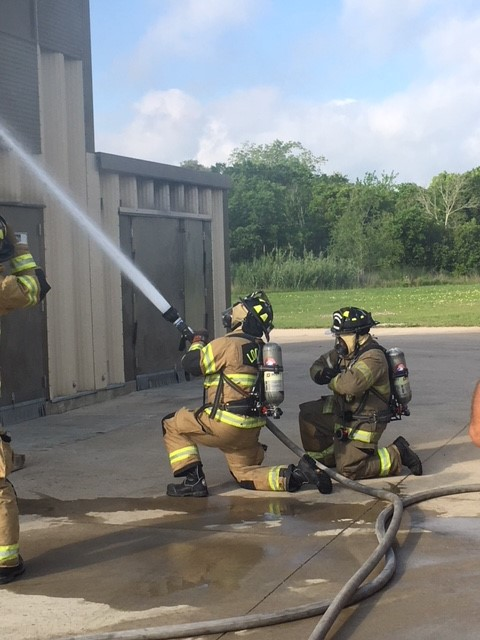 Firefighters spraying water hose